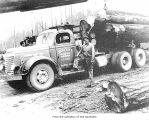 Man with loaded and parked log truck, probably on the Olympic Peninsula