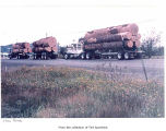 Log trucks parked on a roadside, possibly on the Olympic Peninsula