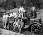 People posing with a car, probably on the Olympic Peninsula