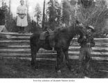 Man with horse near a girl on a fence, probably in Jefferson County