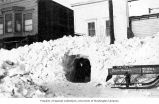 Unidentified man coming out of a snow tunnel on McKinley Street, Valdez, April 20, 1918