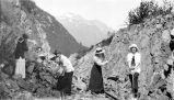 Four women holding pickaxes and other tools clearing rocks on the tracks of the Alaska Northern...