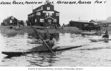 Two kayakers paddling in Kayak Races, and floatplane at right, Kotzebue,  n.d.
