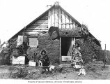 Eskimo women with children in front of sod and plank house, Nome, ca. 1905