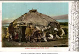 Alaskan Eskimo family outside winter hut constructed of whale bones, sod and walrus and seal...