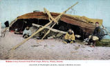 Eskimo ivory carvers seated under boat at camp on beach, Nome, ca. 1905