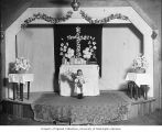 Interior of church showing girl holding flowers and dressed for confirmation, 1905