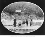 Five Kinugmiut Eskimo boys standing on beach below a house on a hillside, Cape Prince of Wales,...