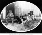 Kinugmiut Eskimo boy holding a cat with five dogs next to him, Cape Prince of Wales, Alaska, ca....