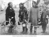 Eskimo berry pickers showing three women and boy in street with pail full of berries, Nome, ca....