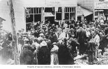 Crowded street scene with Tenakee Pool Room, Alaska Studio, and Liberty Theater visible,...