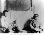 Kingikmiut Eskimo children working on net and holding books while seated inside schoolhouse, Cape...