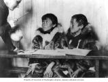 Susan R. Bernardi teaching geography lessons to two Kingikmiut Eskimo boys, To quont'nuk and...