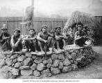 Igorrote men sitting on stone platform inside a replica village at the Lewis and Clark Exposition,...
