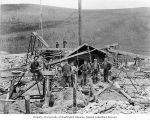 Group of unidentified men standing around mining equipment at claim No. 18 Below Discovery at...