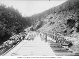 Porcupine Gold Mining Company flume under construction with workmen laying planks on sills,...