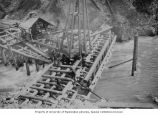 Porcupine Gold Mining Company flume under construction with workmen cutting end of sills for...