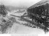 Porcupine Gold Mining flume posts and spillway covered in the snow, Porcupine, Alaska, ca. 1908