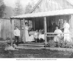 Four unidentified women, two children and one man standing on the porch of the manager's house of...