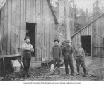 Ike Williamson and three crewmen from the Porcupine Gold Mining Company standing outside a wooden...