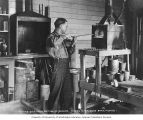 Unidentified man melting gold in a workroom with a furnace and tools, Nome, Alaska, ca. 1907
