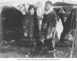 Unidentified Inuit man and woman standing in front of a native dwelling, Alaska, ca. 1906