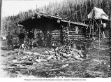 Four men and a woman standing in front of a log cabin with firewood in foreground and tent...