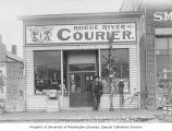 Two unidentified men standing in front of the Rogue River Courier building, Grants Pass, Oregon,...