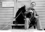 Man and pet bear probably at the U.S. Army or Naval base at Captain's Bay, Dutch Harbor, ca. 1943