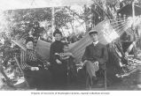 Group of people seated in a hammock including Mrs. A.E. Voorhies holding a child, Louie Marian...