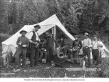 Group of men and two women with cooking utensils eating  a meal at a tent encampment, Alaska, ca....