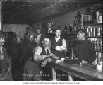 Saloon interior showing a man and others with gold dust and scale, Dawson, Alaska, autumn 1899