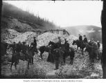 Group of men and women on horseback visiting a gold mining operation near Dawson, Yukon Territory,...