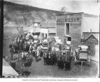 Horses and wagons loaded with goods in front of Wilson's freightering service,  Dawson, Yukon...