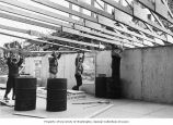 Men lifting roof trusses onto walls of Health Center during construction, Little Diomede, Alaska,...