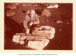 Andrew Gronholdt looking at petrified wood, Unga Island, Alaska, October 1961