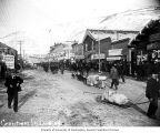 Businesses and dogsleds on the main street in Dawson, Yukon Territory, ca. 1900