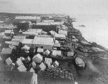 Looking down the Nome spit showing tents and buildings on the beach with the Bering Sea on the...