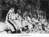 Seven Piegan Blackfeet men seated with blankets along a log bench, Glacier National Park, Montana,...