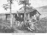 Five miners with gold pan outside of a log cabin, location unknown, ca. 1920