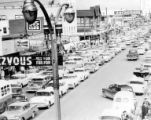 Line of automobiles on Fourth Avenue during the Fur Rendezvous, Anchorage, ca. 1956-1960's