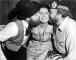 Men kissing a woman during Mr. Fur Face contest at the Fur Rendezvous festival, Anchorage, ca....