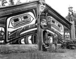 Woman and man standing on steps of the Clan House at Totem Bight State Historical Park, Alaska,...