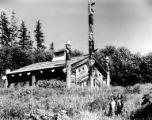 Children standing in grass in front of the Clan House at Totem Bight State Historical Park,...