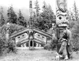 Man and woman with dog looking at the Clan House at Totem Bight State Historical Park, Alaska, ca....