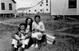 Jamie and Blanche Montgomery and Charlie Killian seated outdoors in Ekuk, ca. 1944