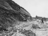 Workers removing dirt from hillside above Alaska Railroad grade at Mile 208, near Talkeetna,...