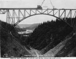 Crane placing last section of arch on Hurricane Gulch Bridge on the Alaska Railroad, Alaska,...