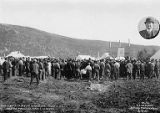 Land auction audience and auctioneer at Nenana with inset photograph of Harry E. St. George, the...