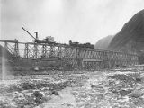 Alaska Railroad workers using crane mounted on work train to remove Alaska Northern Railway Bridge...